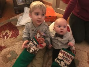 Two little boys with traditional knit christmas stockings